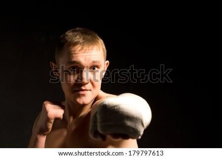 Determined young boxer throwing a punch at the camera with a bandaged fist as he practices for a fight on a dark background - stock photo