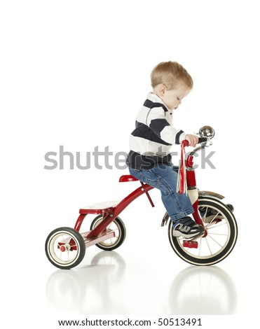 Determined young boy riding his tricycle - stock photo