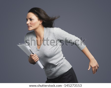 Determined young businesswoman running into the wind against gray background - stock photo