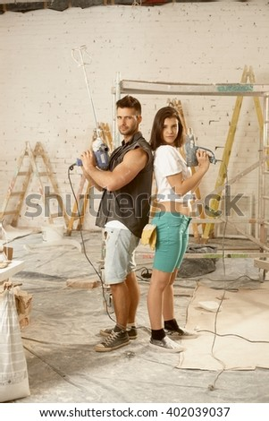 Determined young couple looking serious holding power drill, renewing home. - stock photo