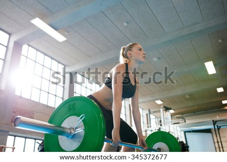 Determined young fitness woman training with heavy weights. Caucasian female athlete doing weight lifting workout in gym. - stock photo