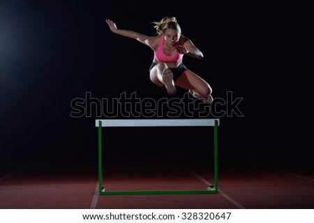 Determined young woman athlete jumping over a hurdles - stock photo