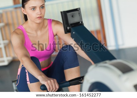 Determined young woman working out on row machine in fitness studio - stock photo