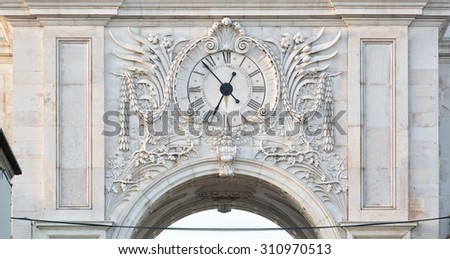 Detial of the old, decorated clock above the gate of Rua Augusta,  leading to Commercio Square, the historical spot in Lisbon, capital of Portugal - stock photo