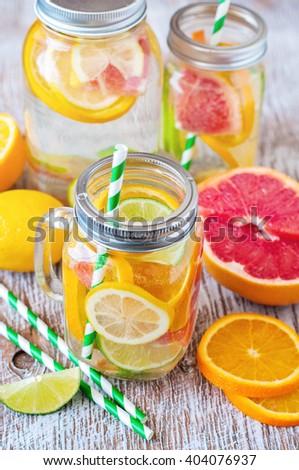 Detox citrus fruit, summer homemade lemonade cocktail, infused flavored drink water, refreshing beverage, toned image, selective focus - stock photo
