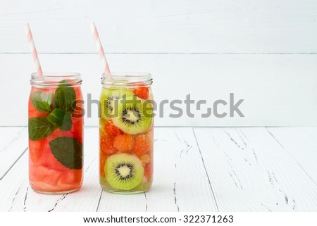 Detox fruit infused flavored water. Refreshing summer homemade cocktail. Clean eating. Copy space background - stock photo