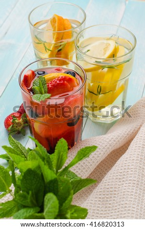 Detox fruit infused flavored water. Refreshing summer homemade cocktail with lemon, orange, strawberries and blueberries - stock photo