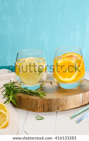 Detox fruit infused flavored water. Refreshing summer homemade cocktail with orange, lemon and rosemary leaves - stock photo