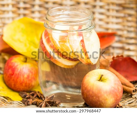 Detox water with apples. Autumn composition with leaves and apples. - stock photo
