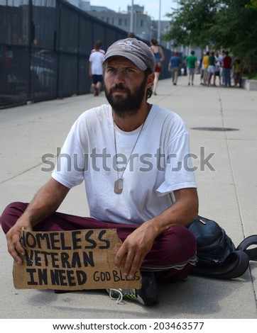 DETROIT, MI - JULY 6: Homeless veteran pauses as he begs for money in Detroit, MI on July 6, 2014 - stock photo