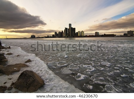 Detroit River still packed with ice blocks, seen from Windsor, ON. The dramatic sky of the nice but cold afternoon seems to converge all to Detroit downtown. - stock photo