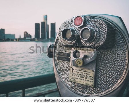 Detroit Sightseeing Skyline. Sightseeing tourist binoculars overlooking downtown Detroit, Michigan on a summer afternoon from Windsor, Ontario, Canada. - stock photo