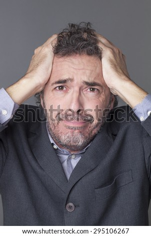 devastated businessman holding his head with both hands crying and expressing dramatic mistake at work - stock photo