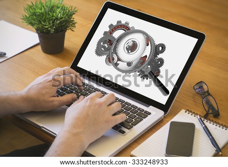 Developer or web designer at work. Close-up top view of man working on laptop with magnifying glass analyzing gears on screen. all screen graphics are made up. - stock photo