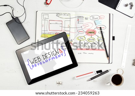 Developer workplace. Open notepad with hand drawn website project. Tablet PC from above - stock photo