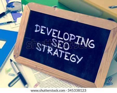 Developing SEO Strategy Handwritten on Chalkboard. Composition with Small Chalkboard on Background of Working Table with Ring Binders, Office Supplies, Reports. Blurred Background. Toned Image. - stock photo