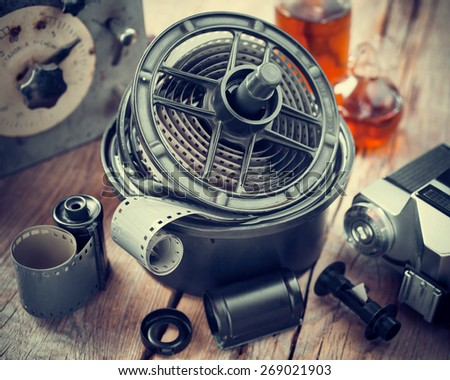 Developing tank with its film reels, photo film rolls, cassette, retro camera and chemical reagents. - stock photo