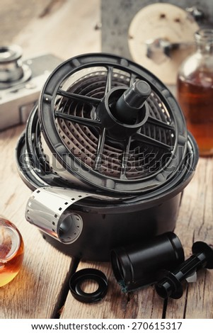 Developing tank with its film reels, photo film rolls, cassette, vintage camera and chemical reagents on wooden desk. - stock photo
