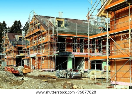 Development construction site with 3 houses in scaffolding - stock photo