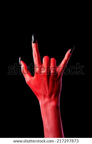 Devil hand showing heavy metal gesture, isolated on black background   - stock photo