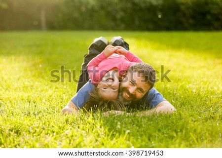 Devoted father and daughter lying on grass, enjoying eachothers company, bonding, playing, having fun in nature on a bright, sunny day. Parenthood, lifestyle, childhood and family life concept.  - stock photo