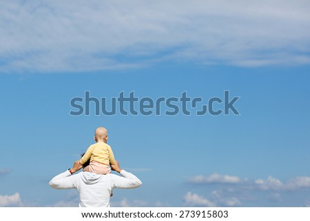Devoted mother and baby cuddling, spending bonding quality time observing bright blue cloudscape. Attentive parenting and family lifestyle concept. Nature and people background.  - stock photo