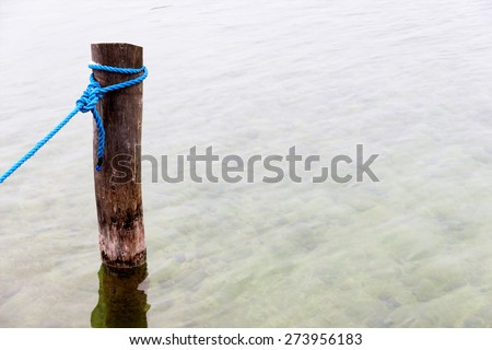 dew on a wooden pole, symbol of reliability, security, nautical, harbor - stock photo