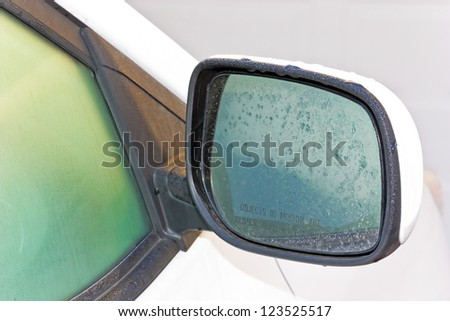 Dew on the mirror. Closeup of morning dew drops on a car side mirror. Mirror view is on the passenger side. - stock photo