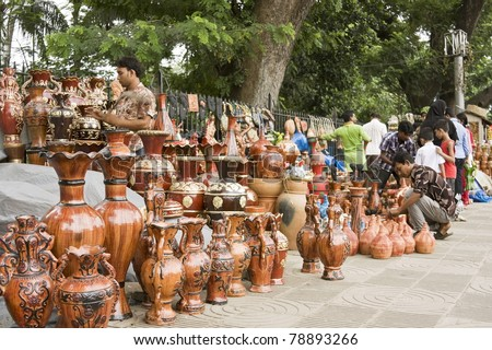 DHAKA, BANGLADESH – SEPTEMBER 21: Clay-made pottery on display in a roadside handicraft shop on September 21, 2010 in Dhaka, Bangladesh. Shops like this sell handmade pottery to tourists and locals. - stock photo