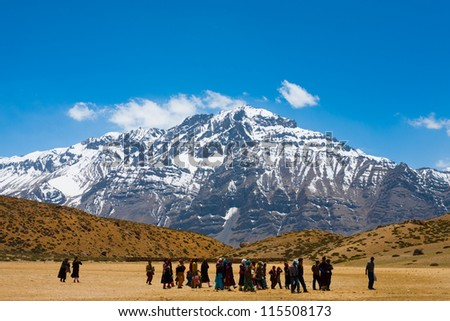 DHANKAR, INDIA - JUNE 7: An unidentified group of Buddhist pilgrims walk on pilgrimage to a holy lake among the Himalayan mountains in the Spiti Valley on June 7, 2009 in Dhankar, India - stock photo