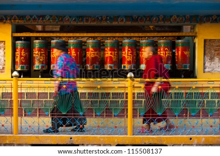 DHARAMSALA, INDIA - JUNE 22: Buddhists in motion blur, spin prayer wheels near the home of the Tibet's Dalai Lama, a pilgrimage point, on June 22, 2009 in Dharamsala, India - stock photo