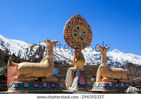 Dharma Wheel (Dharmachakra). Buddhist wheel of life on the roof of a temple in nepal. The rooftop statues of two golden deer flanking a Dharma wheel. - stock photo