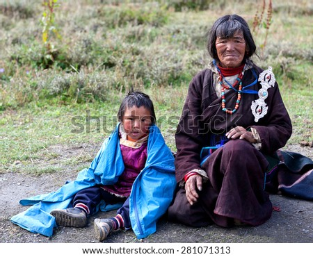 DHO TARAP, DOLPO, NEPAL - SEPTEMBER 11: Drokpa woman in national clothes ant her grandson waiting for Puja ceremony during Full Moon Festival on September 11, 2011 in Dho Tarap village, Nepal - stock photo