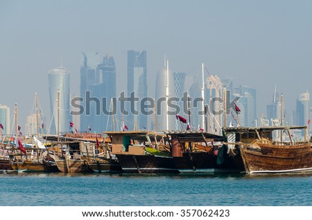 Dhows moored off at the corniche in central Doha, Qatar, Arabia, with some of the buildings from the city's commercial port in the background. - stock photo