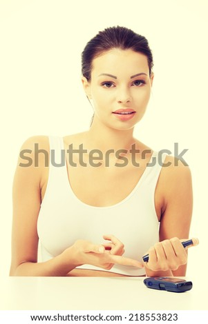 Diabetes patient measuring glucose level blood test using ultra mini glucometer and small drop of blood from finger isolated on a white background - stock photo