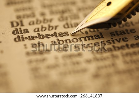 Diabetes pen nib pointing to the words in the dictionary, shot with very shallow depth of field, - stock photo