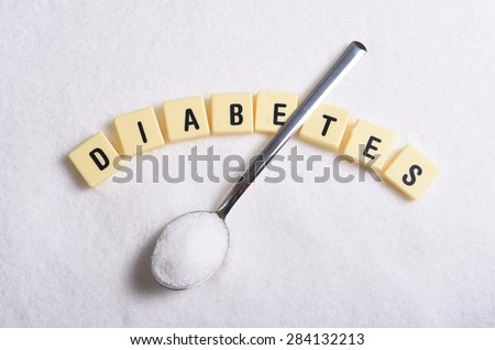 diabetes word in crossword style block letters and spoon or teaspoon over grainy white sugar texture background in health care and healthy nutrition concept - stock photo