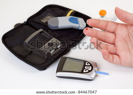 Diabetic woman doing a blood test with the necessary equipment in the background. - stock photo