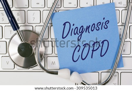 Diagnosis COPD - blue note paper with text on computer keyboard with stethoscope - stock photo