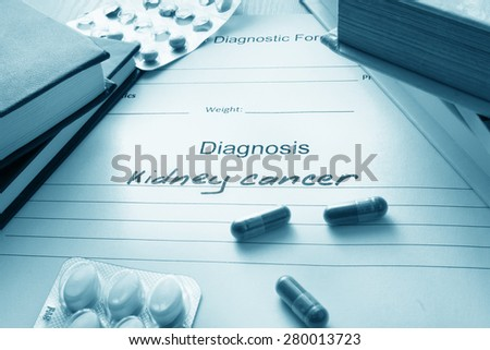Diagnostic form with diagnosis kidney cancer and pills. - stock photo