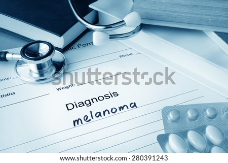 Diagnostic form with diagnosis melanoma and pills. - stock photo