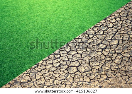 Diagonal composition of half of the frame with lush green grass and the other half is cracked dry soil background. - stock photo