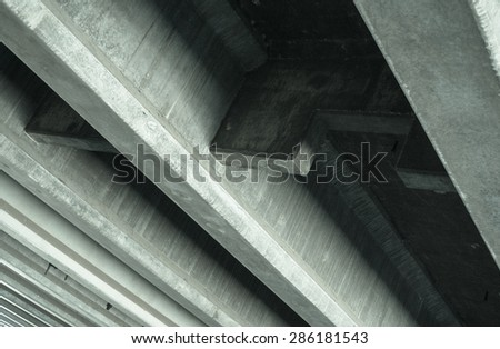 Diagonal lines run parallel under an interstate overpass. - stock photo