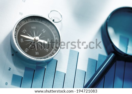 Diagram concept with compass and lens in blue toning - stock photo
