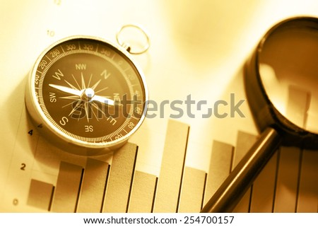 Diagram concept with compass and lens in sepia toning - stock photo