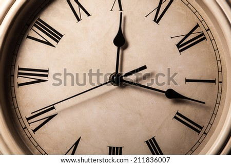 dial with Roman numerals and arrows close up - stock photo