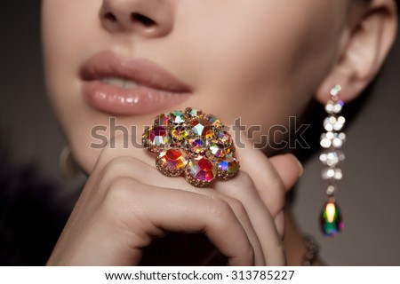 Diamond. Brilliant. Antique old vintage earrings and ring. Jewelry on her finger at the girl close-up on a  - stock photo