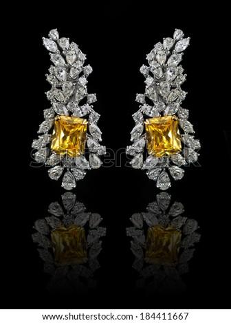 Diamond Earrings on a black reflective background  - stock photo