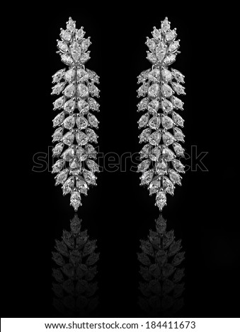 Diamond Earrings on a black reflective background  - stock photo