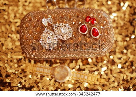 Diamond fashion earrings on golden purse with strass and gems. sequins sparkling sequined textile - stock photo